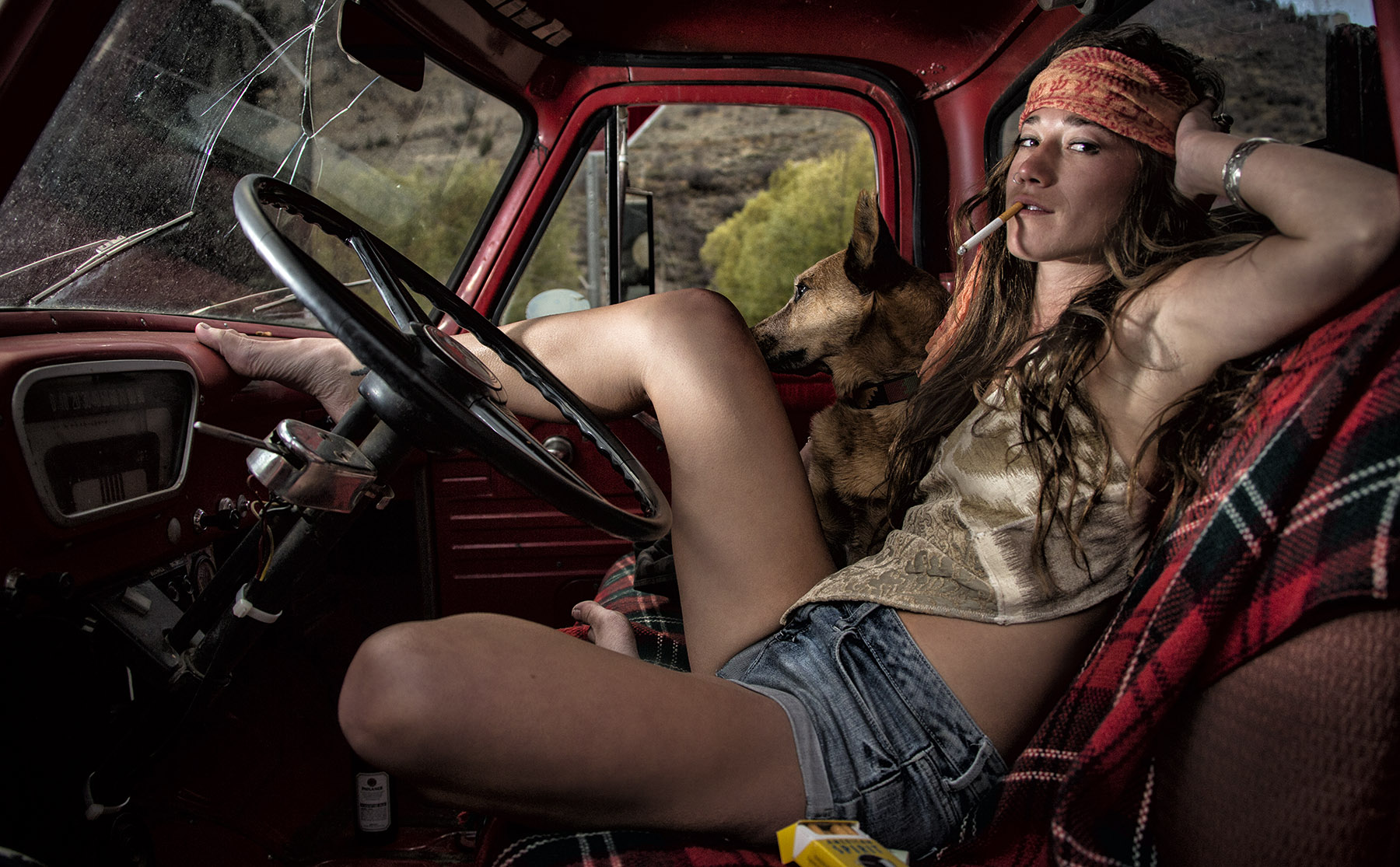 Hippie girl and dog in old truck